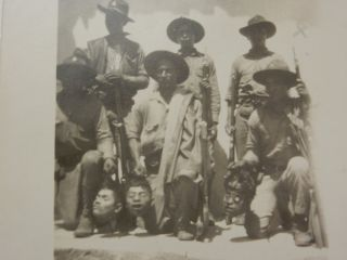 Real Photo Postcard (RPPC) depicting six soldiers (probably the Nicaraguan National Guard) holding the heads of three decapitated bandits